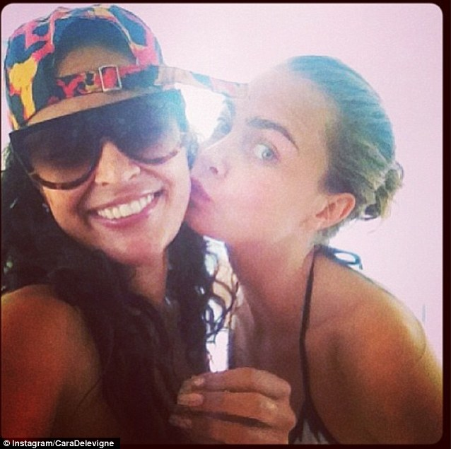 Cara kisses a friend with her trademark brows more prominent than ever against her perfectly (make-up free) smooth skin