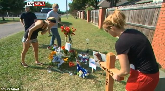 Grieving: Sarah Harper (at left in a black headband) visits a memorial of flowers and mementos that has been created at the spot where he was shot and killed on Friday