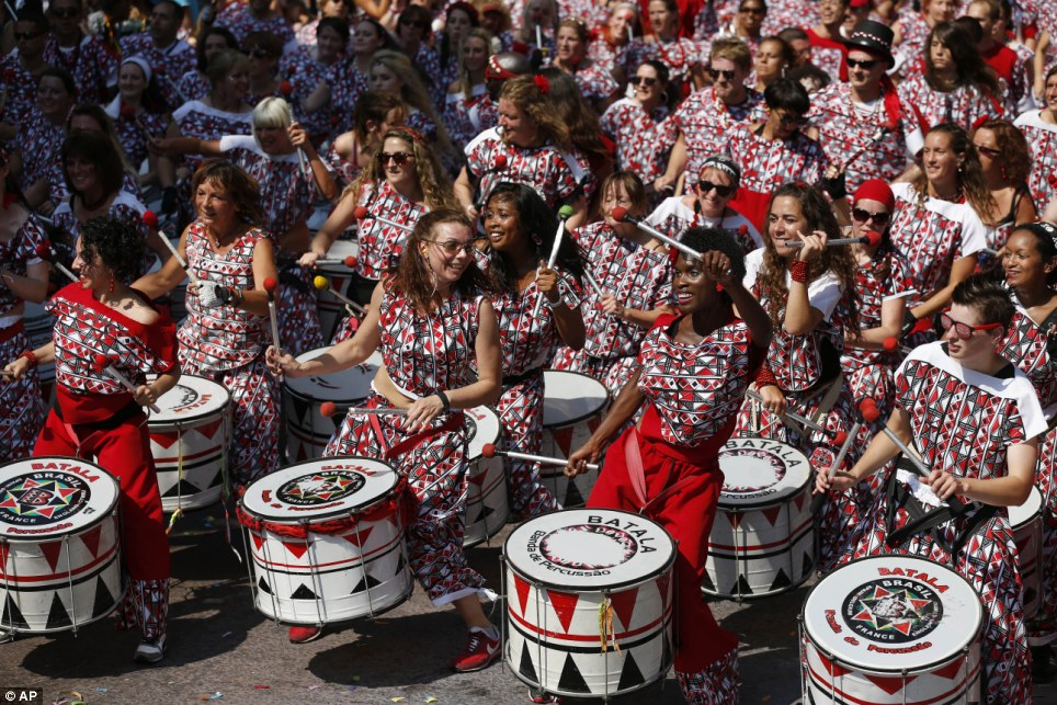 Beat of my drum: A Brazilian percussion troupe parade through the streets as onlookers and dancers move to their beat