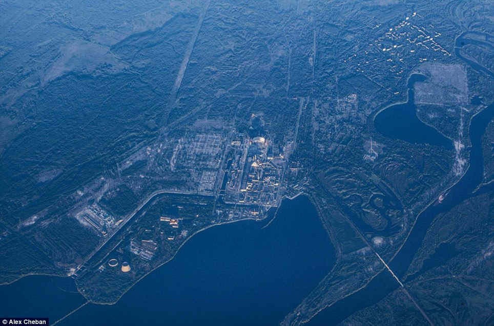 Eerie: This picture shows the city of Pripyat, top right, and the Chernobyl power plant, centre surrounded by the forest