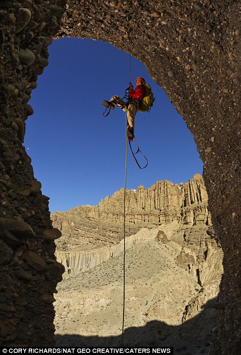 A scientist hoists himself up at a Mustang cave entrance