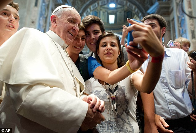 Seen it all before: The teenage pilgrims show Pope Francis their technology - but it appears he is well in tune with modern life