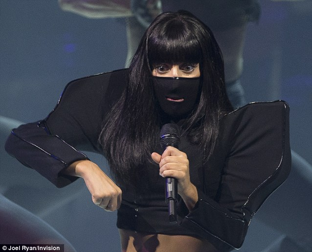 Finish him: Gaga dressed as a black ninja, putting on a black wig and balaclava