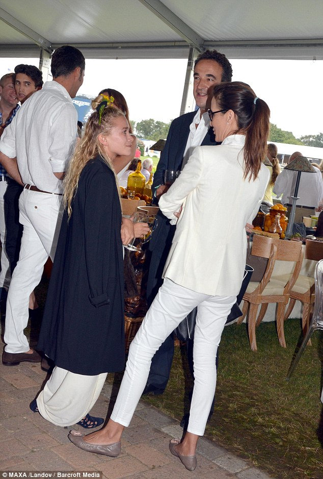 Quirky style: She drowned her tiny frame in white trousers and a white top, covering up with a baggy long black jacket paired with blue heels