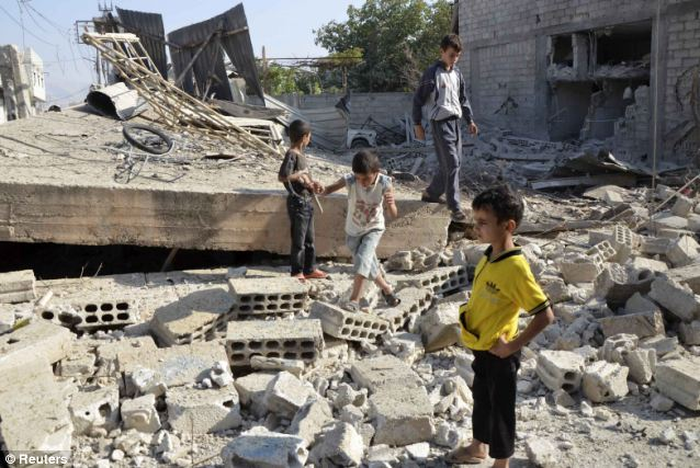 Troubled: Boys walk on the rubble of a building hit by what activists said was shelling by forces loyal to Syria's President Bashar al-Assad, in the Duma neighbourhood of Damascus as fighting continues