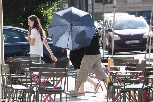 Under her umbrella: Kristen's legs were just visible as she walked behind an umbrella to the set