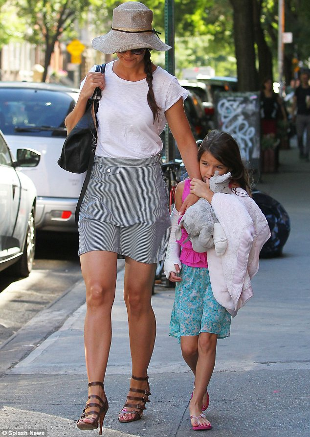 Hold on tight: Suri used her ininjured arm to hold onto her mother, favourite cuddly toy and a blanket