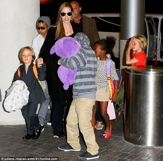 The whole brood: Pax carried his favourite bear from Legoland California as the family made their way to their flight