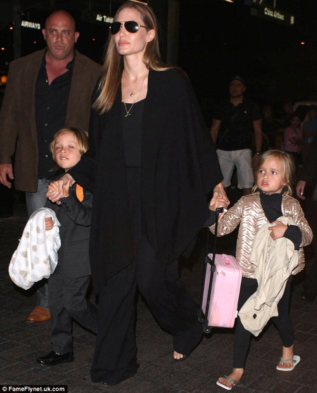 Keeping them close: Angelina took charge of her two youngest children, five-year-old twins Knox and Vivienne, by holding one of each of their hands