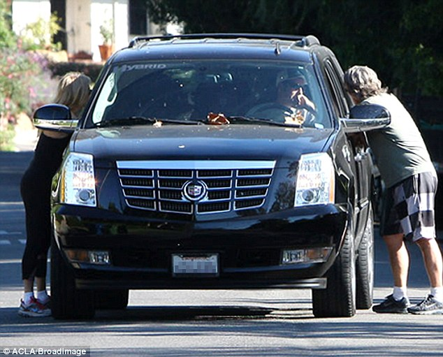 Keep it brief: Adam Sandler, Goldie Hawn and Kurt Russell stopped for a quick chat together in the middle of the road