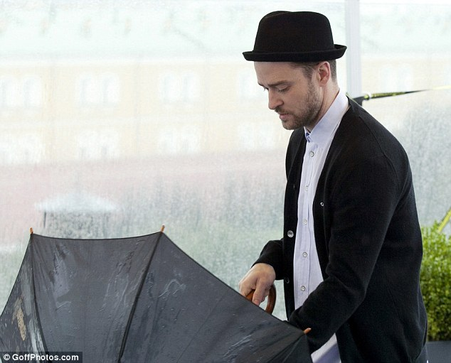 Dressed for it: Luckily the Friends With Benefits actor came prepared and kept his head dry under a black hat