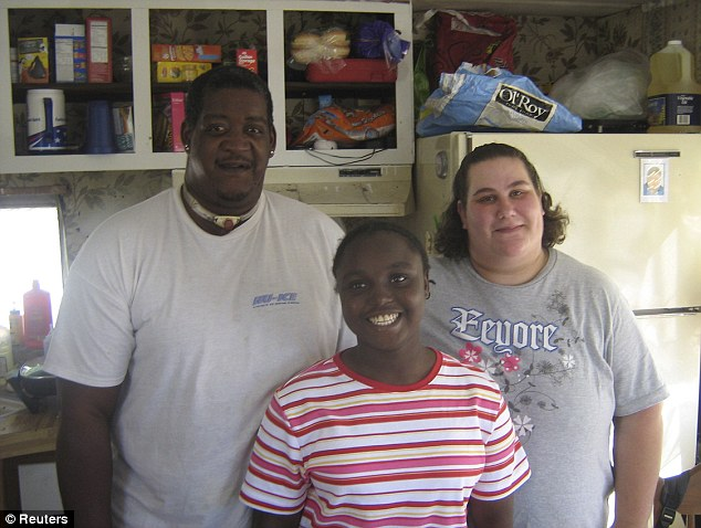 Private re-homing: Quita, middle, with Calvin and Nicole Eason - the couple her adoptive parents sent her to live with when they no longer wanted to raise the teenager from Liberia