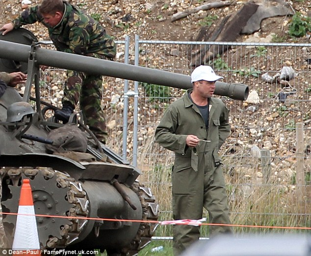 And action! Brad Pitt shot scenes for his new film Fury, dressed in wartime khaki overalls, but would not disclose his new haircut hidden under a white baseball cap