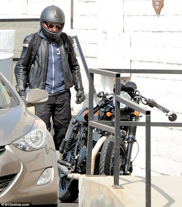 Layered up: Bradley piled on the clothes for his ride with a hooded sweatshirt and leather jacket