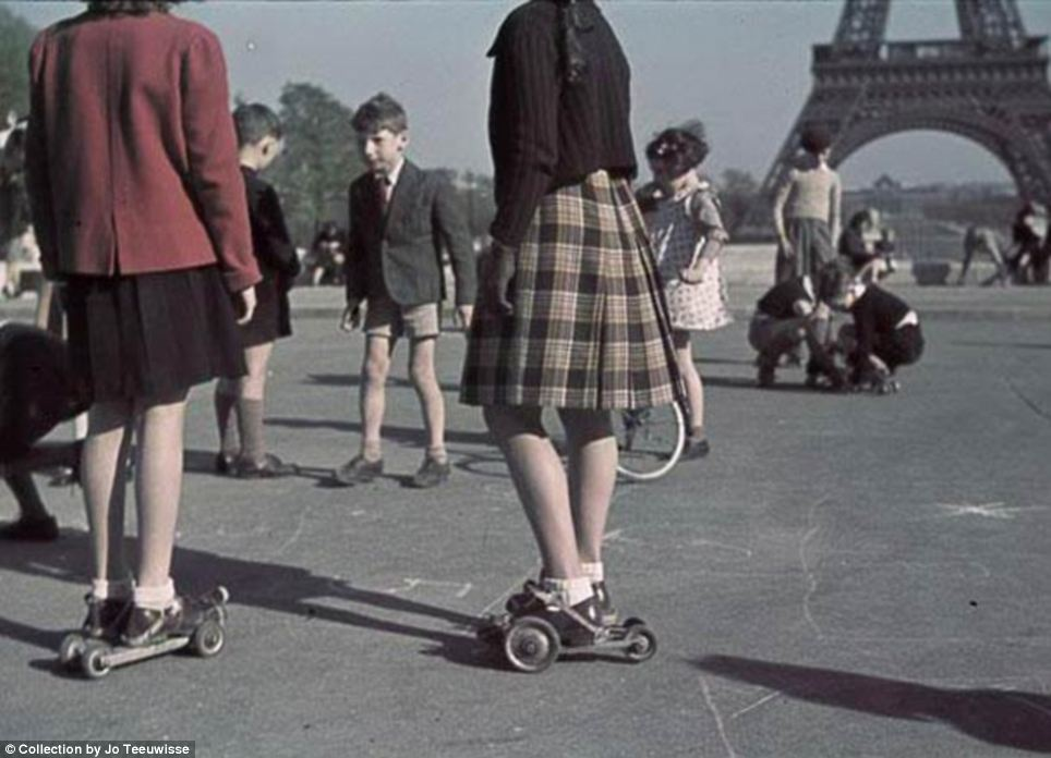 Too young to understand: Girls and boys play in what appear to be the early forerunners of rollerskates against the backdrop of the Eiffel Tower on central Paris's Champ de Mars
