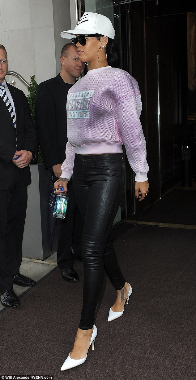 Singer turned designer: Rihanna paired her cheeky sweater with some skin tight leather trousers and white heels