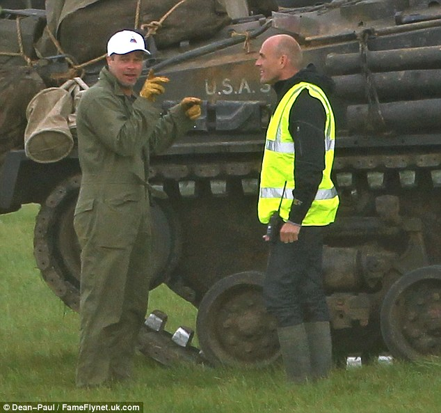 Time for a quick chat: Brad was seen chatting to a member of the production crew whilst standing beside a USA tank