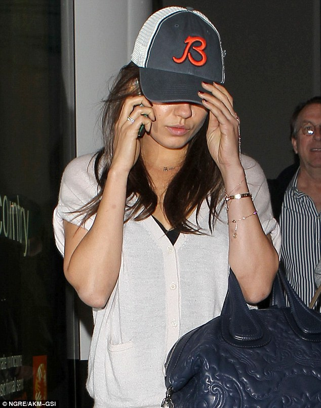 Keeping a low profile: Mila left LAX wearing a blue baseball cap pulled down low over her famous face