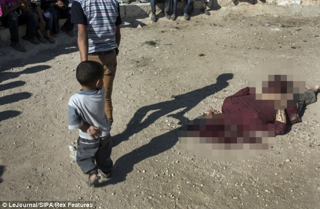 A Syrian boy is held by the hand as he walks past the body of a beheaded Islamic militant loyal to Assad