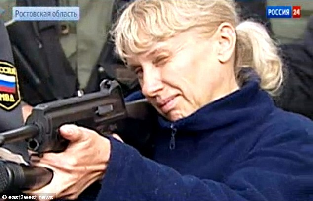 Family affair: Former kindergarten teacher Inessa Tarverdiyeva, 46, demonstrates to police how she used a gun to kill her victims