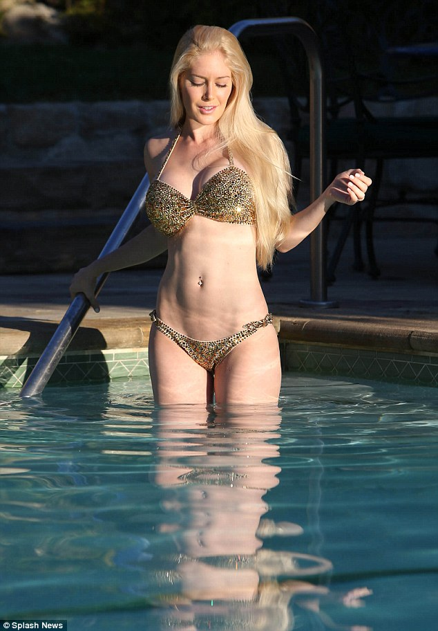 Water nymph: The former reality star stood in the water while showing off her bountiful assets in a garish, gold-sequin bikini