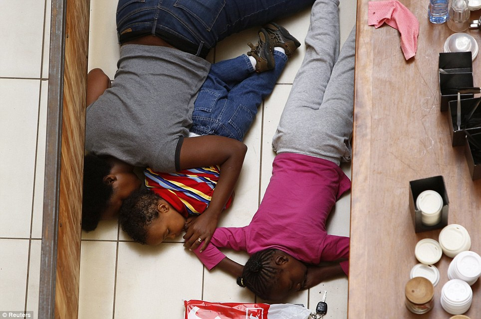 Protection: A mother and her children lie on the floor as they attempt to hide while the gunmen armed with automatic weapons go on the rampage