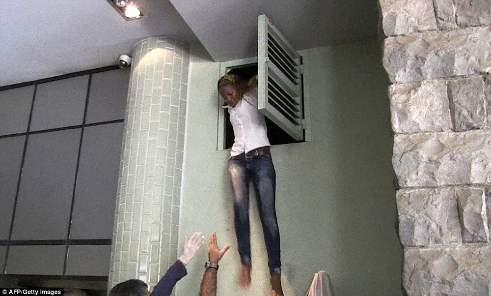 Desperation: A crowd of people hold their arms out to catch a Kenyan woman as she jumps out from the air vent where she had been hiding from the gunmen