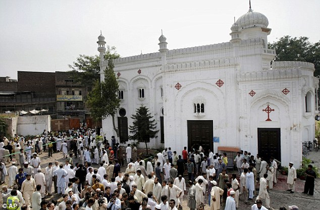 People gather at the site of suicide attack on a church in Peshawa
