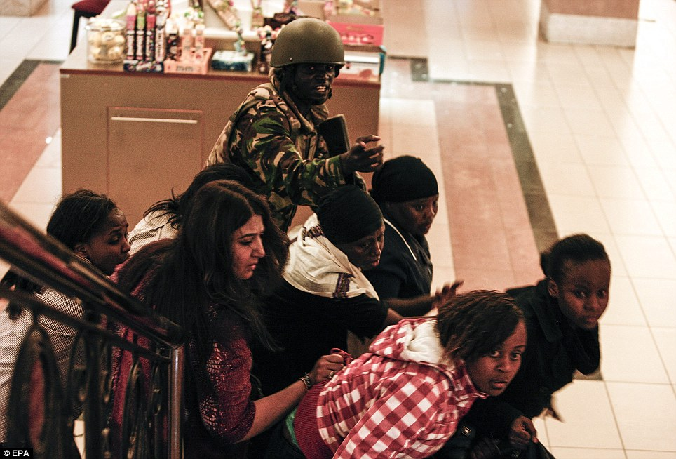 Fleeing to safety: A soldier directs people up stairs inside the Westgate shopping mall after a shootout in Nairobi, Kenya