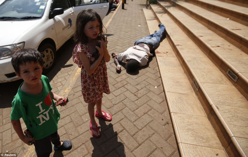 Terrified children wait by the body of a man after escaping from the shopping centre. Militants have today threatened to kill the remaining hostages