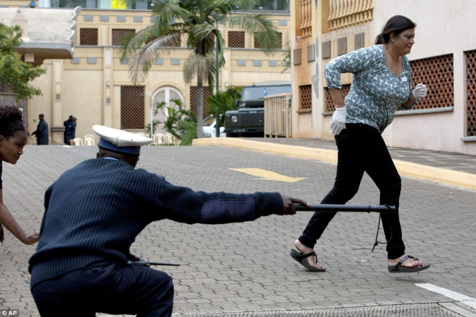 A paramedic runs for cover outside the mall in Nairobi after a large explosion was followed by sustained shooting