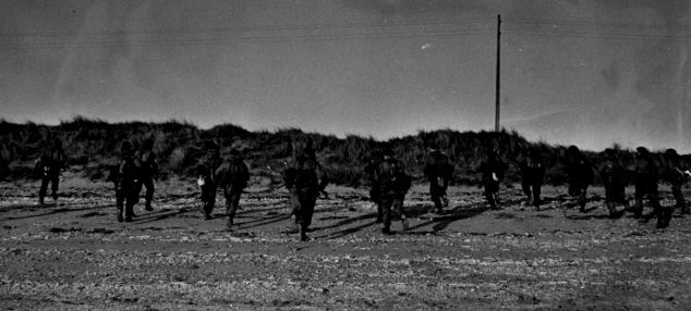 These Royal Marines are captured running for cover in silence before sunrise on the crucial day