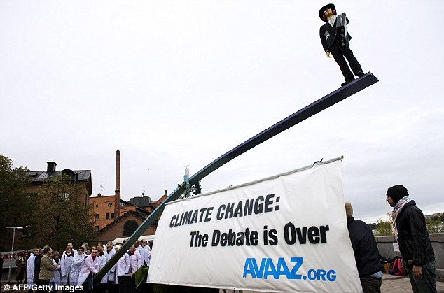 Difference of opinion: Activists gather outside the the United Nation's Intergovernmental Panel on Climate Change in support of the group's findings