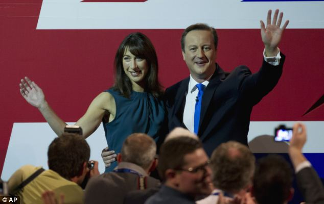 Patriotic: Mr Cameron posed with wife Samantha in front of a large union flag as the Tory faithful gave him a standing ovation