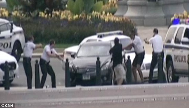 Surrounded: Police officers surround the car with their weapons drawn after the female driver rammed a barricade close to the White House on Thursday