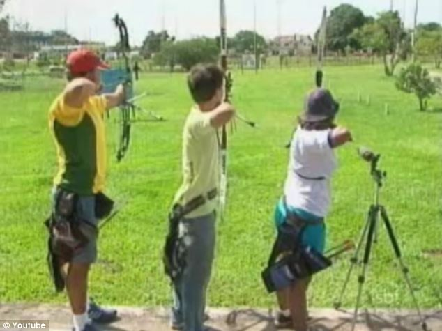 Ready, aim, shoot: Three youngsters line up and prepare to shoot their arrows at a distant target