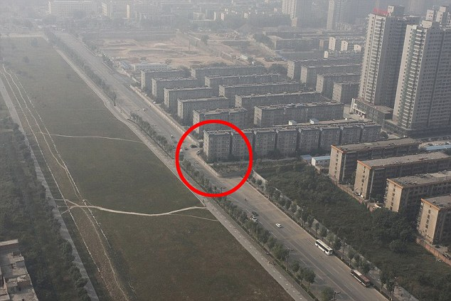 Town planning disaster: Chinese officials were forced to cut this motorway in half to go around a block of flats after the building was accidentally erected in its path before the road was built