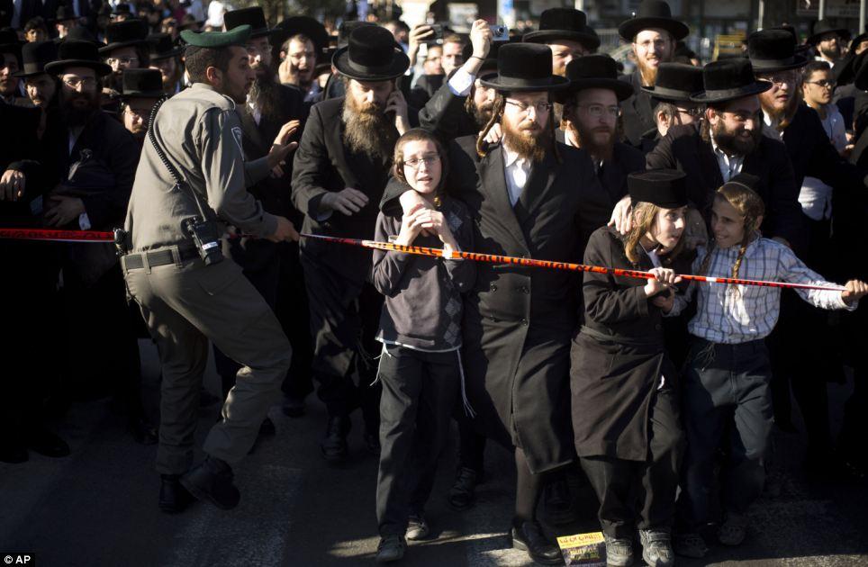 Lutte: Un agent de la police des frontières israélienne tente d'arrêter les hommes et les enfants orthodoxes d'atteindre le véhicule