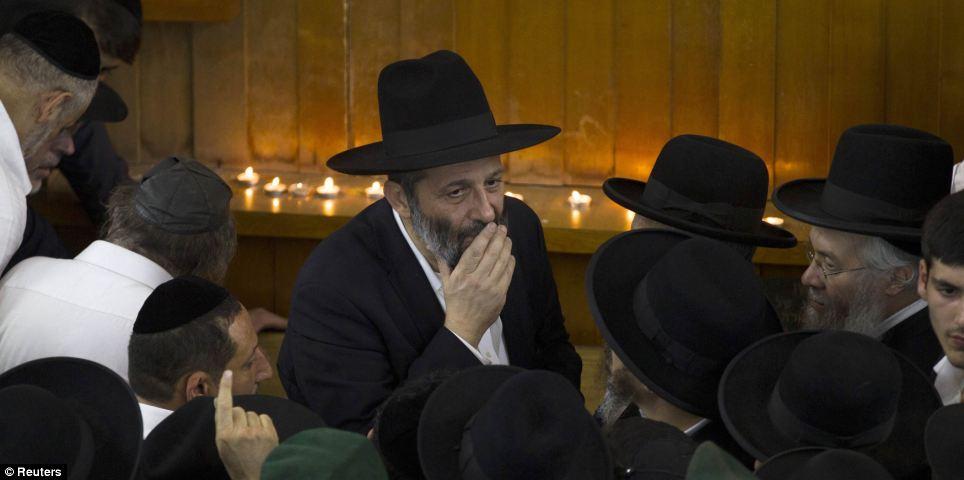 Arye Deri (au centre), chef de file du parti ultra-religieux Shas, regarde près du corps du rabbin Ovadia Yosef