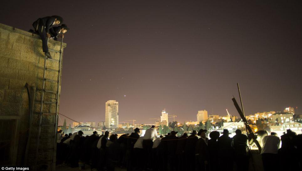 Pleureuses juifs observent l'enterrement sur tous les toits que la nuit descend