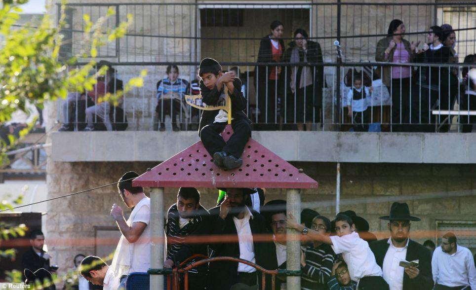 Fixant des maisons: les femmes prennent du recul sur leurs balcons comme des hommes et des garçons inondent les rues pour montrer leurs respects