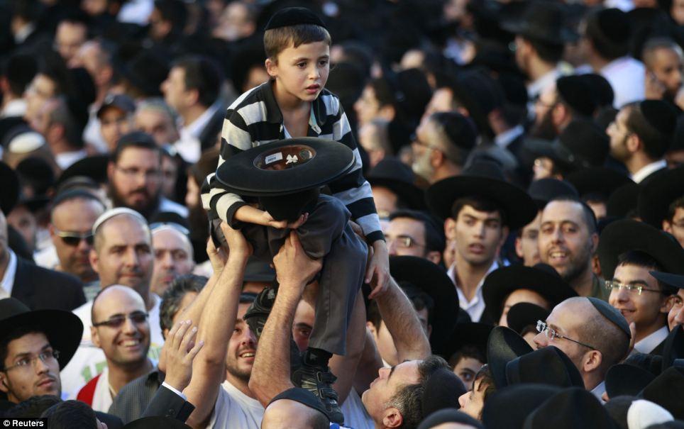 Accablé: Un petit garçon a l'air accablé comme il est reporté sur la foule observant le corps d'un chef religieux charnière être effectuée par