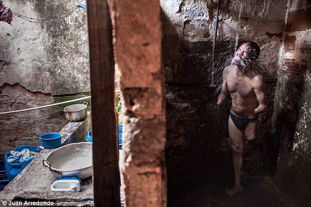 Hardship: A man who has lost both hands and one leg showers in the ruins of a house