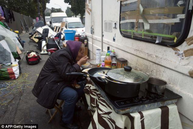 Un miembro de la comunidad gitana se come en un campamento el 18 de octubre de 2013, en Ivry-sur-Seine, en las afueras de París