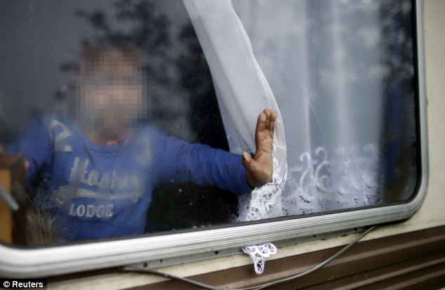 Un niño de Roma se ve en una ventana de una caravana en un campamento de las familias gitanas en Triel-sur-Seine, cerca de París