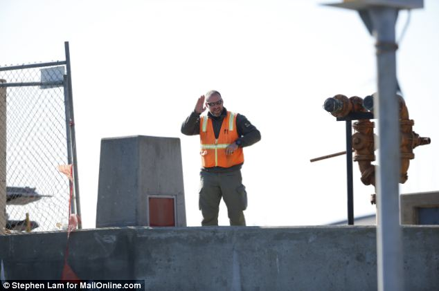 A security guard waves from barge built with four levels of windowed shipping containers at a pier on