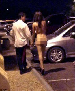 Naked: A second woman decided to don her birthday suit for the festivities and is seen walking through the parking lot with an unidentified man