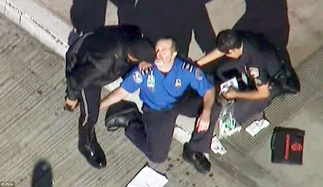 A TSA officer (pictured in the center) gets medical attention after several people were wounded by gunfire at Los Angeles International Airport on Friday by a lone gunman armed with an assault rifle