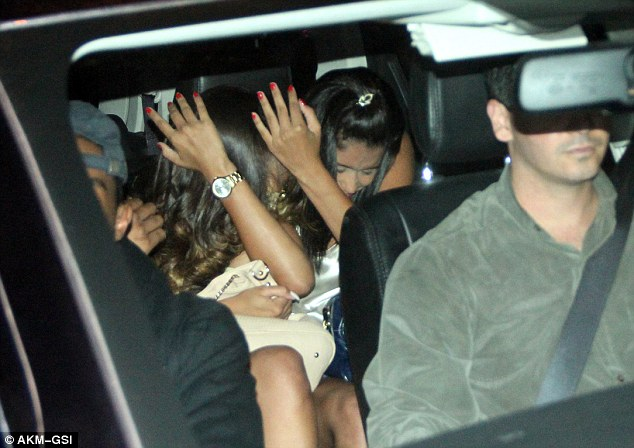 Swift exit: Two ladies from the establishment were seen hiding as they left in a vehicle behind Justin