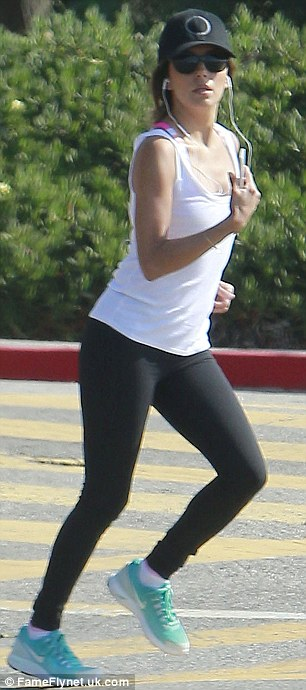 Sporty style: Eva looked as stylish as ever in her white top, black leggings and turquoise trainers
